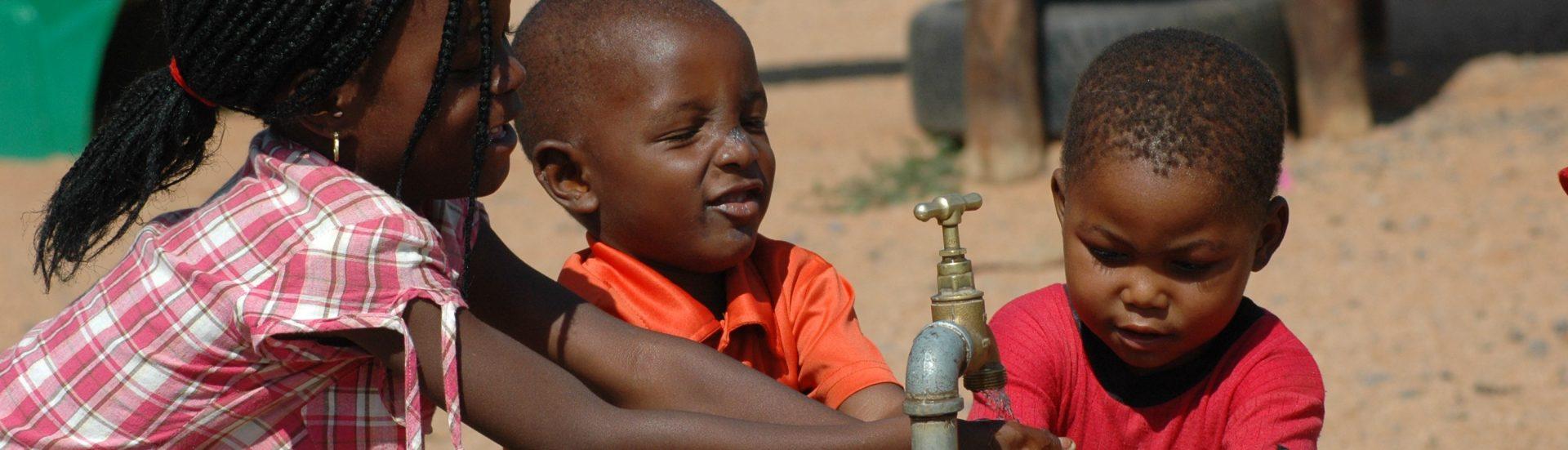 Kinderen bij kraan in Afrika