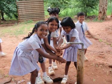 Lachende meisjes wassen handen aan kraan in India