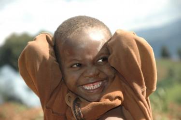 Lachend afrikaans kind met bruine trui