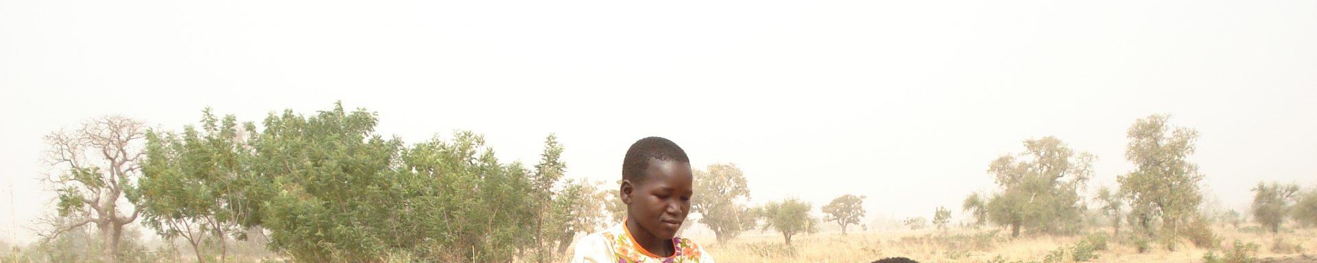 Kinderen gebruiken waterpomp in Burkina Faso