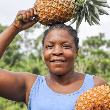 Afrikaanse vrouw met ananas op haar hoofd