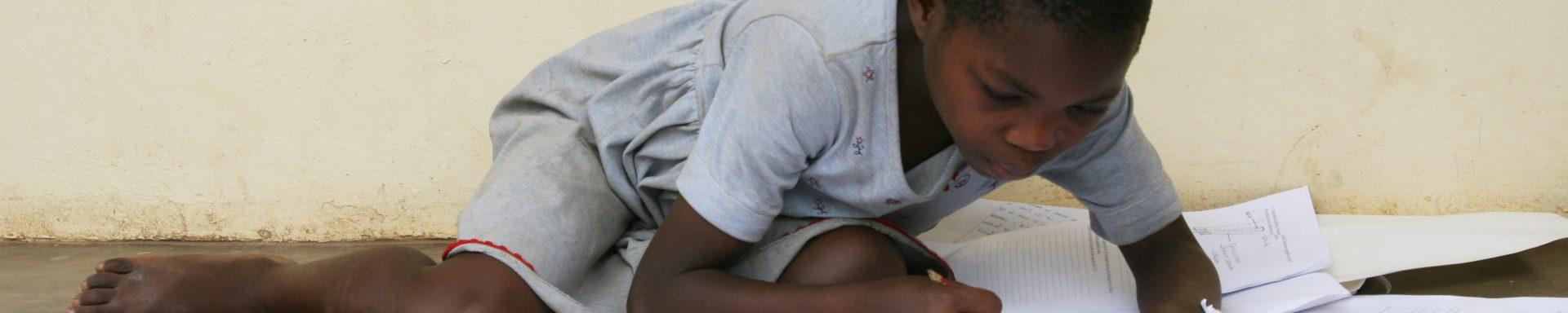 Kind maakt huiswerk op de grond