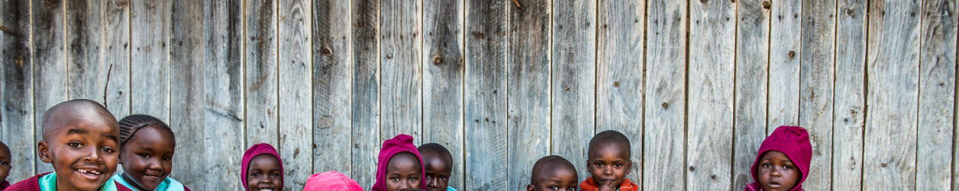 Lachende kinderen uit Kenia in rode kleding