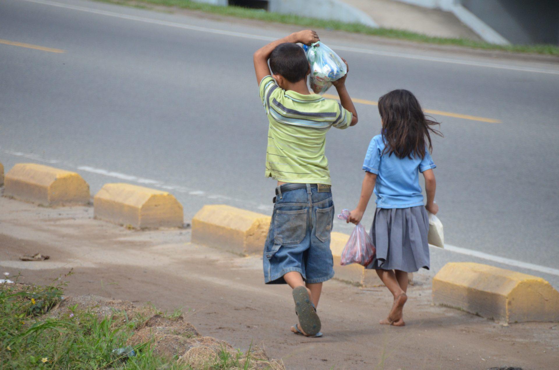 Kinderen lopen langs de weg in honduras