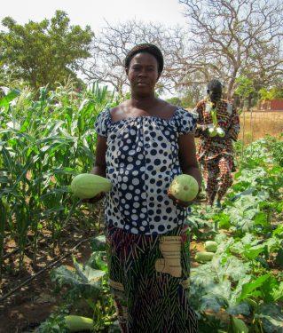 Een vrouw poseert met twee meloenen in Burkina Faso.
