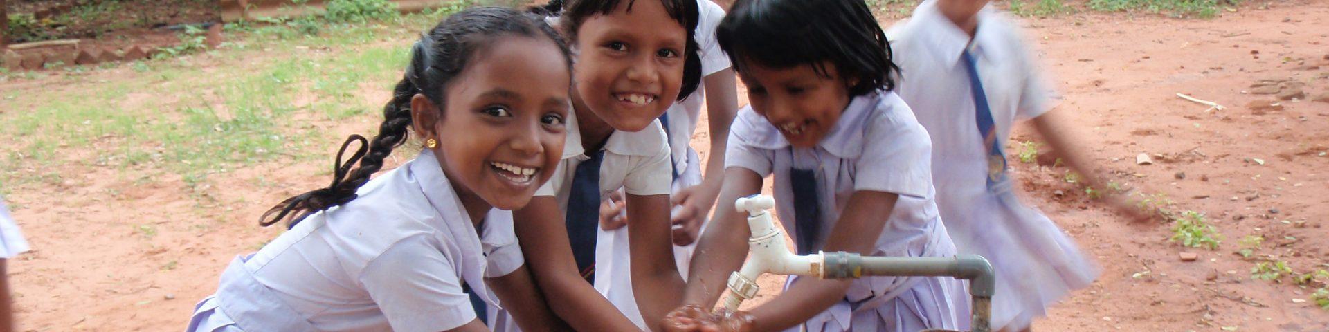 Meisjes wassen handen aan kraan