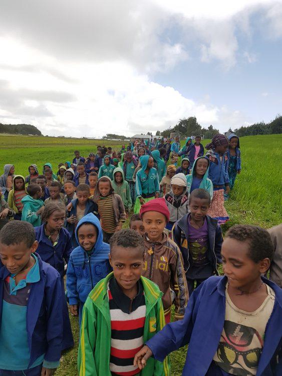 Een grote toeloop van kinderen bij de opening van een waterput in Ethiopië.
