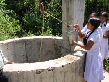 Een meisje haalt water uit een waterput in Sri Lanka.