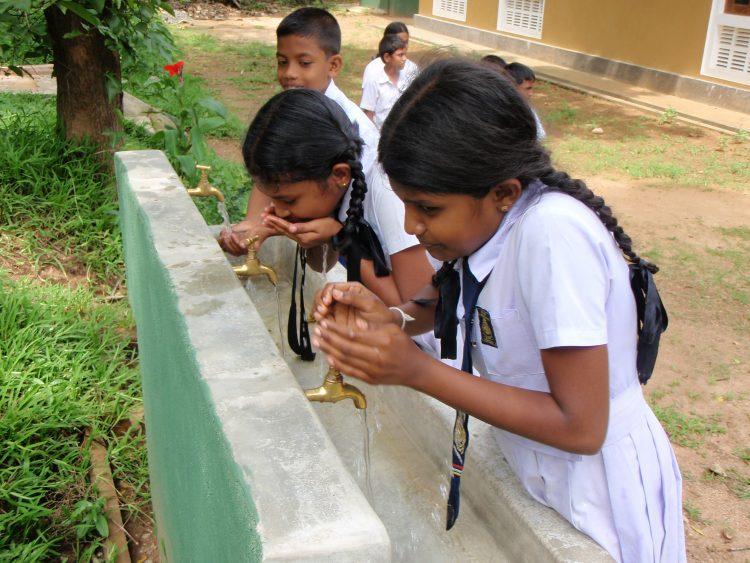 Twee meisjes drinken schoon drinkwater in Sri Lanka.