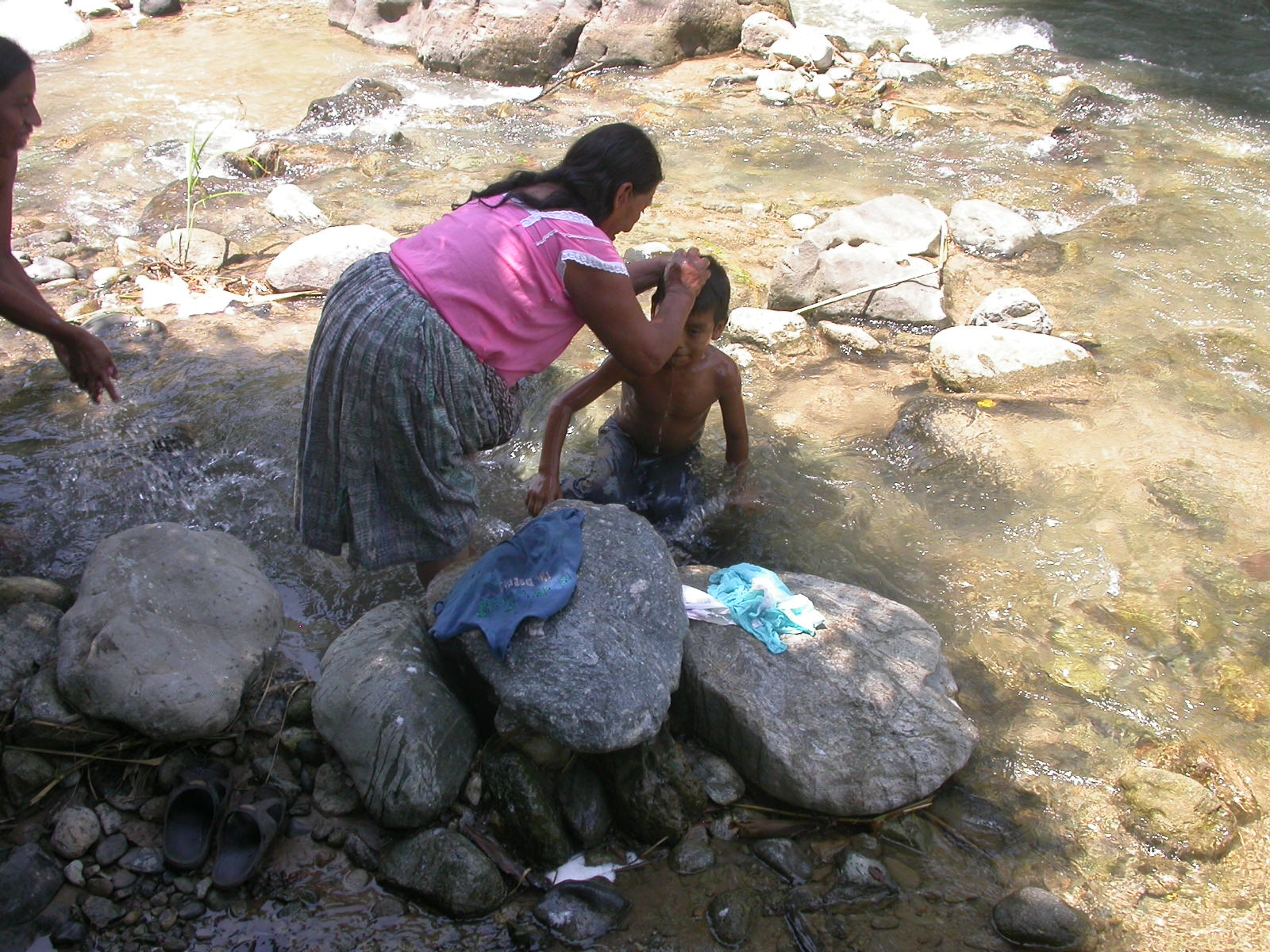 jongetje wordt gewassen in de rivier