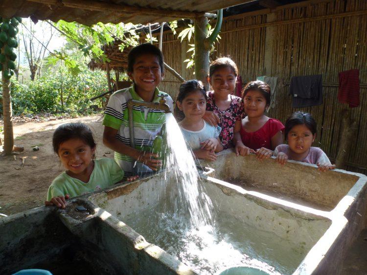 Zes blije kinderen bij een nieuwe kraan in Guatemala.