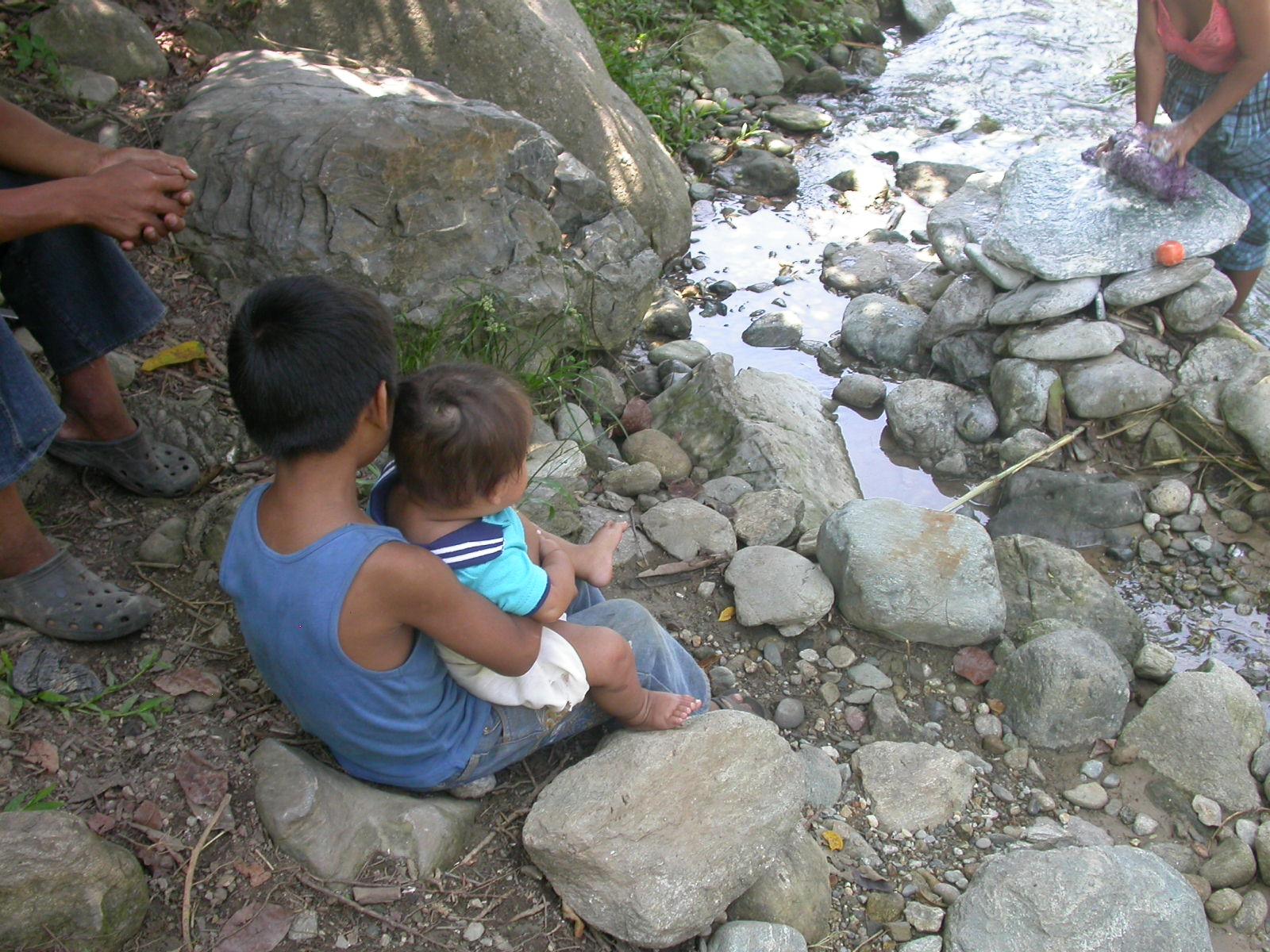 kinderen bij moeders die wassen in de rivier