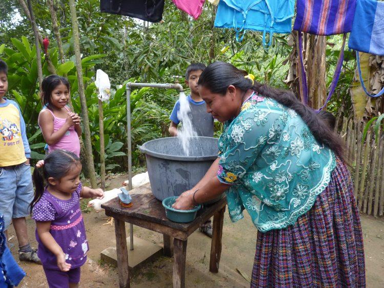 Een vrouw tapt schoon water in een ton in Guatemala