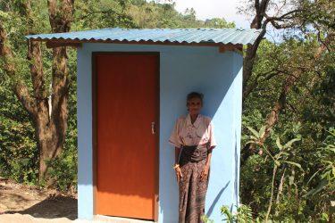 Een oudere vrouw poseert bij een nieuwe wc in Indonesië.
