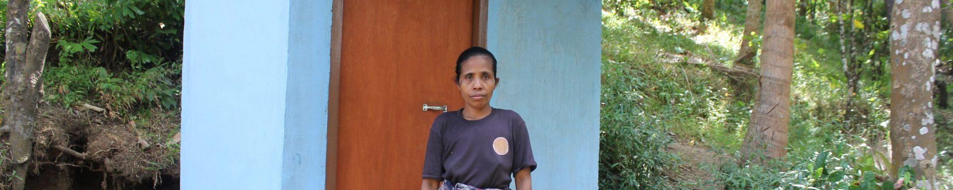 Een meisje poseert bij een nieuw toiletgebouw in Indonesië.