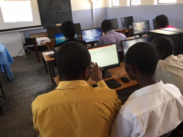 Een klas met mensen die computerles krijgen.