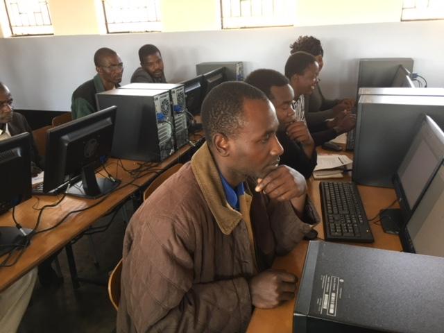 Een leraar krijgt computerles in Zimbabwe.