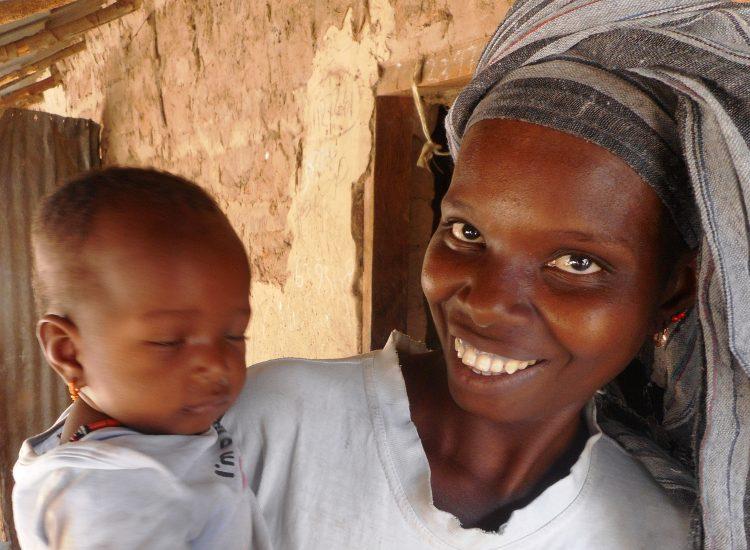Een lachende vrouw met een baby op haar arm in Gambia.