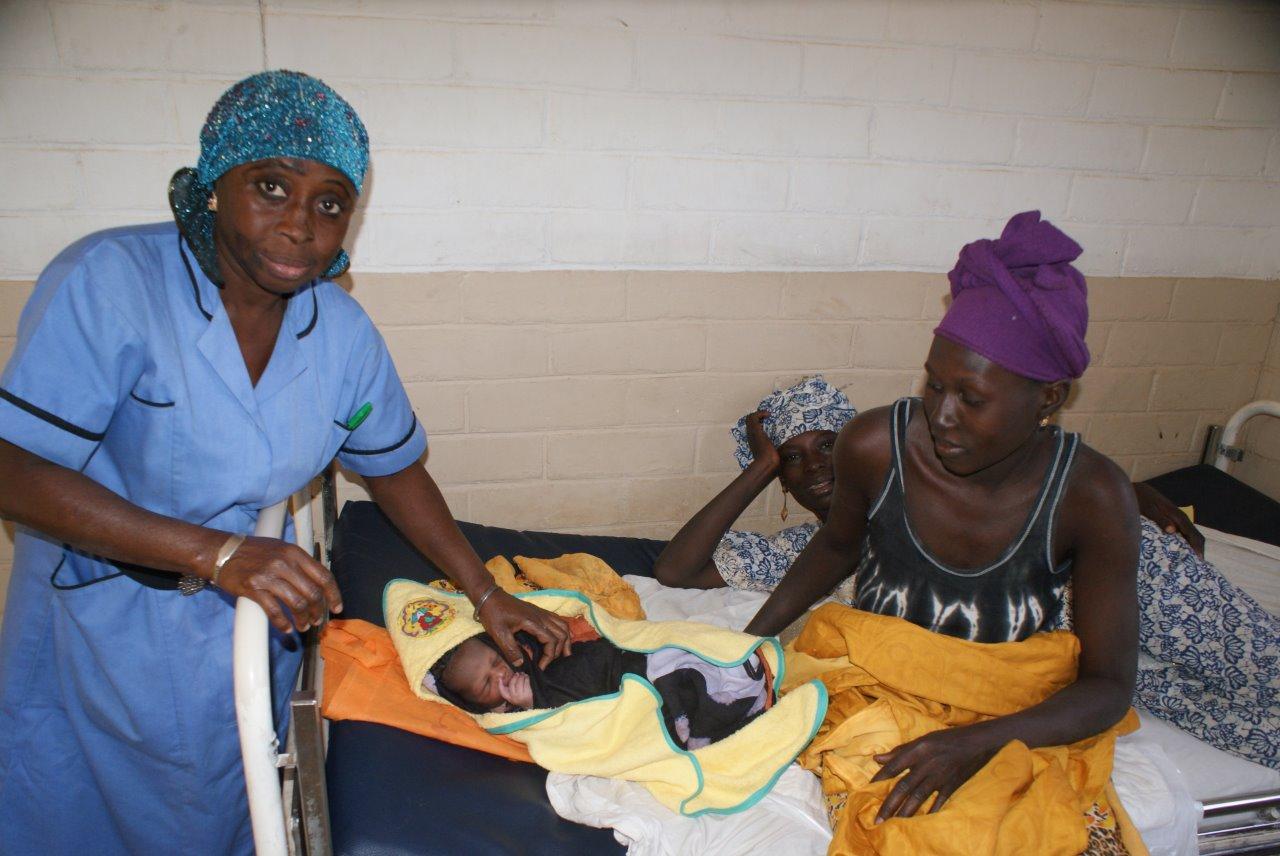 Drie vrouwen met een pasgeboren baby op bed in Gambia.