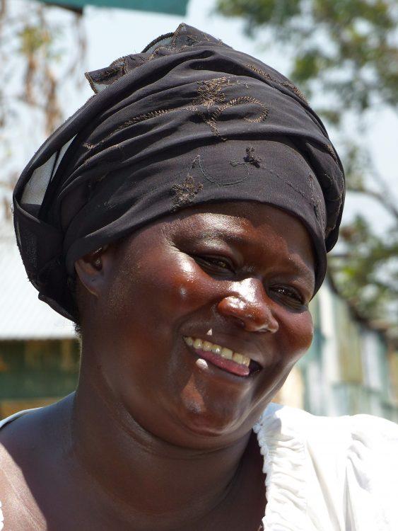Een visservrouw lacht in de camera in West Kenia.