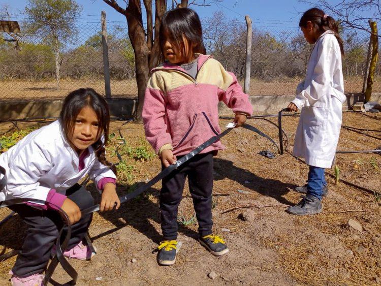 Drie meisjes aan het werk in een moestuin in Argentinië.