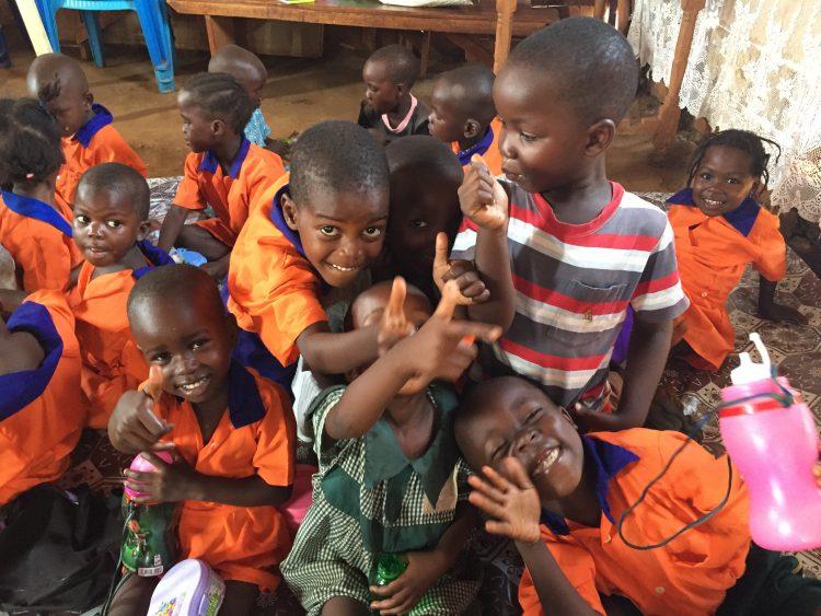 Een groepje vrolijke kinderen op school in Oeganda.