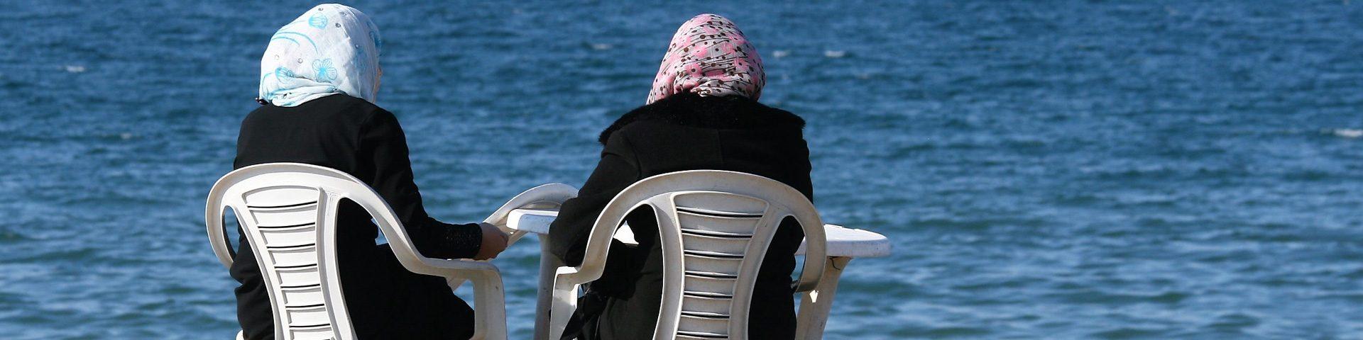 Twee vrouwen in Gaza zitten samen aan het water.