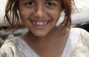 Meisje uit India kijkt in camera.