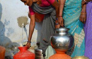 Een vrouw tapt schoon drinkwater in India.