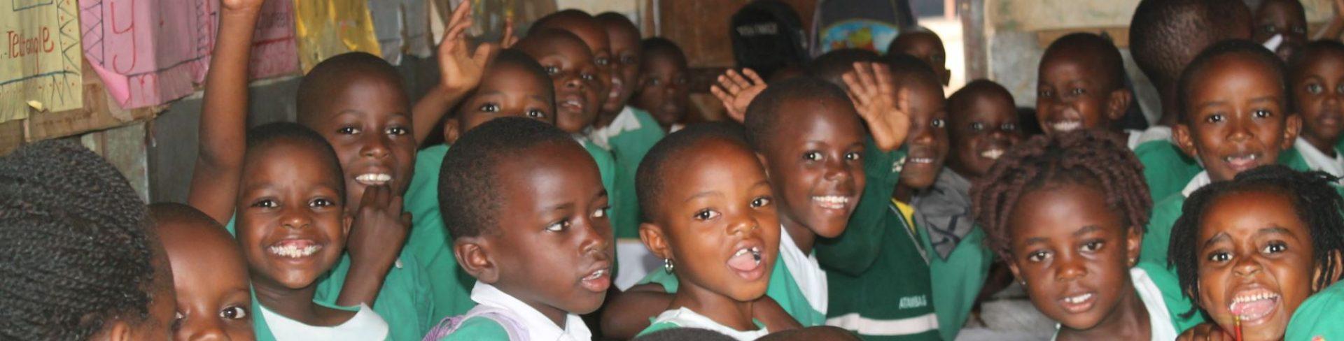 Een klas vol lachende kinderen in Oeganda.