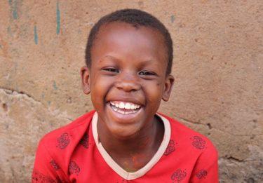 Een jongetje met een rood shirt lacht in de camera in Oeganda.
