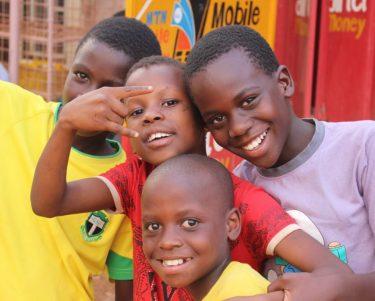 4 jongetjes kijken vrolijk in de camera in Oeganda.