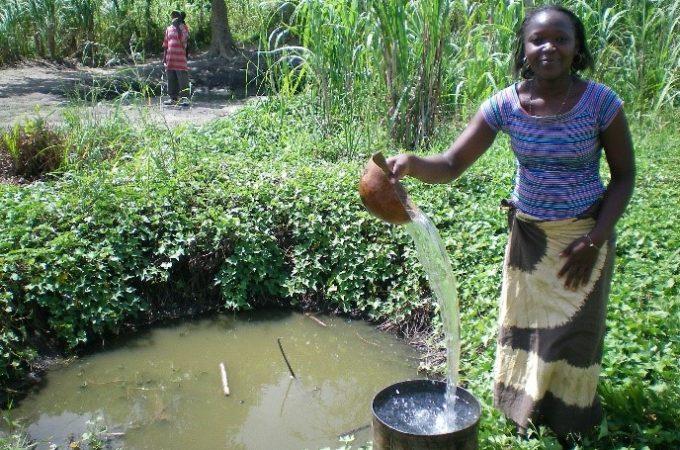 Een vrouw giet schoon water in een emmer in Malawi.