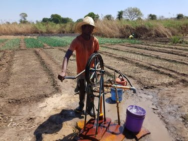 Een man bedient een handwaterpomp in Malawi.