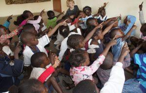 Kinderen op school in Zambia wijzen naar het bord.