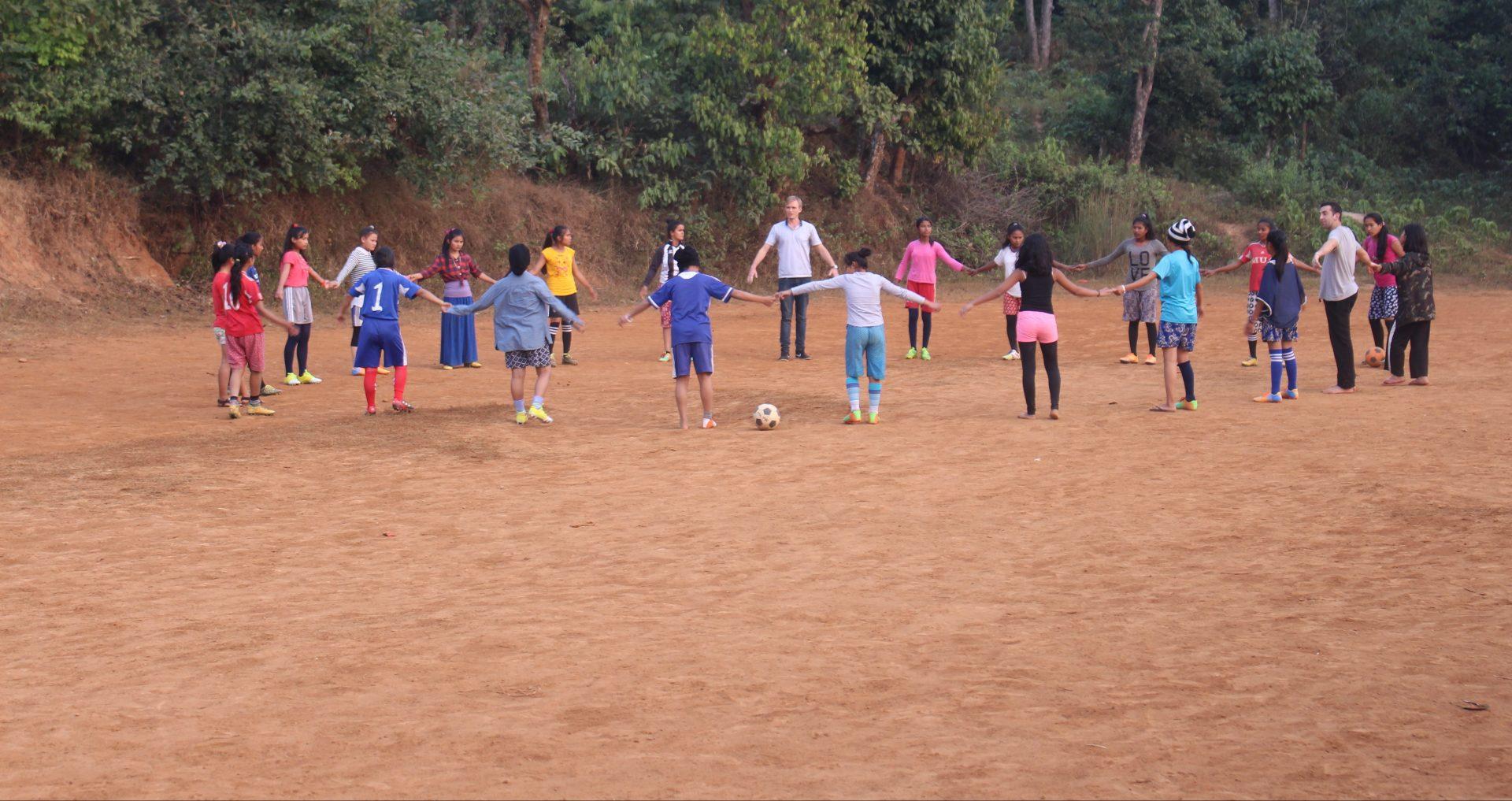 Leerlingen van de Maya Universe Academy in Tanahun spelen buiten voetbal.