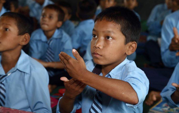 Een jongetje krijgt les in gebarentaal in Nepal.