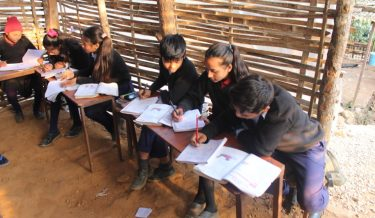 Leerlingen maken huiswerk in een klein klaslokaal in Nepal.