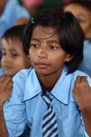 Een meisje oefent handgebaren tijdens een les in Nepal.