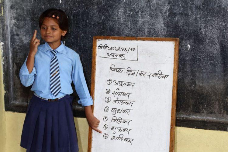 Een meisje staat naast een lesbord op een dovenschool in Nepal.