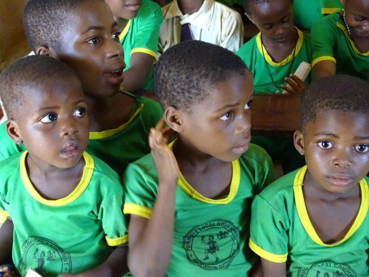 Drie kleine kinderen met groene shirtjes in Nigeria.
