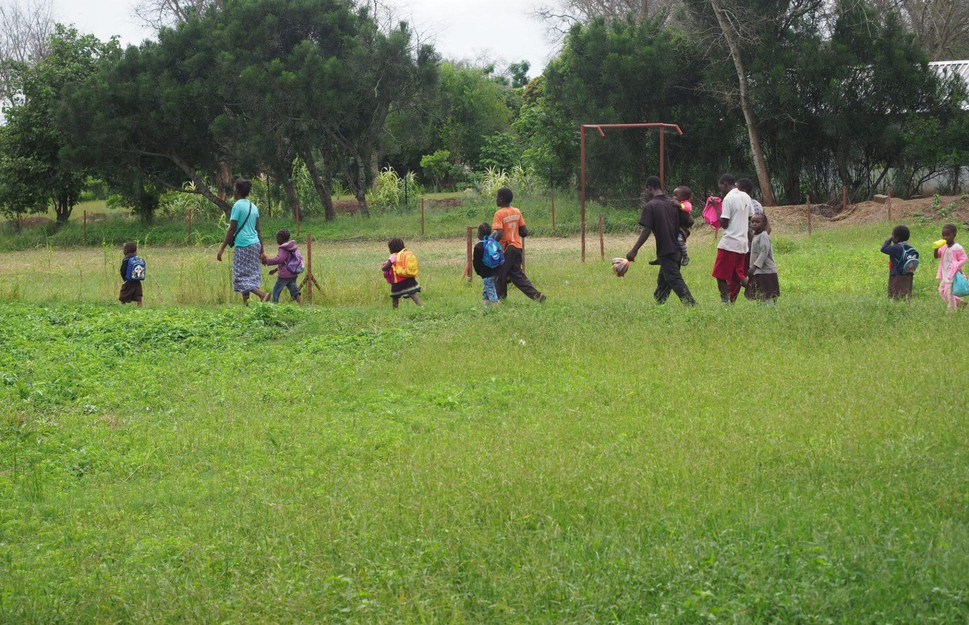 Ouders en kinderen lopen naar school in Zambia.