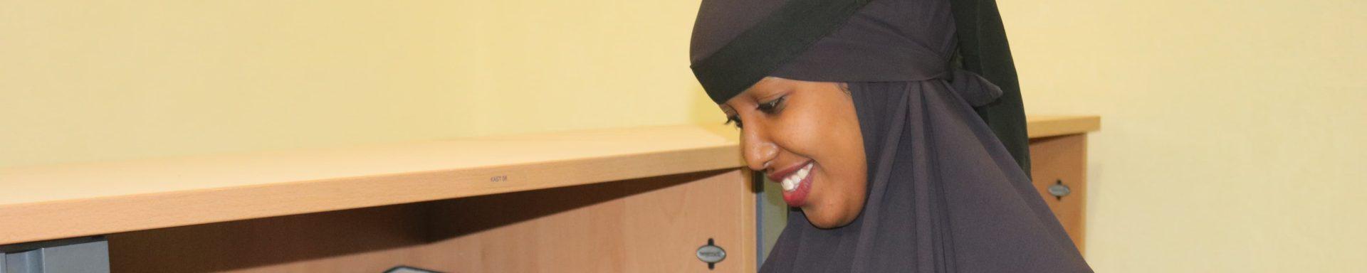 Een vrouw in Somalië kijkt een boek in.