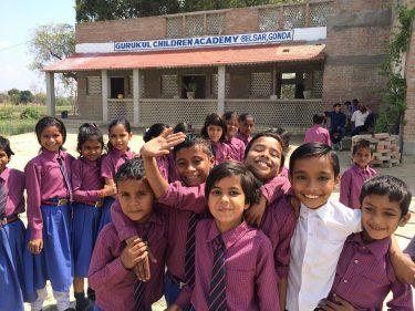Kinderen in paarse schooluniformen voor hun school in India.