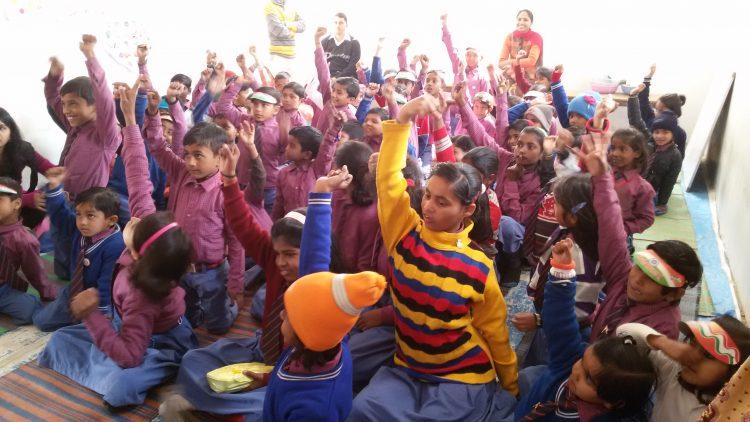 Kinderen steken hun vinger op in de klas in India.