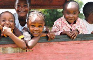 Vier kinderen poseren voor een foto in Zambia.