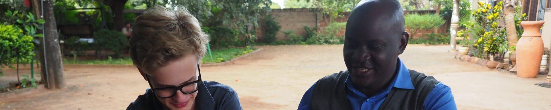 Xavier en Kennedy bekijken bouwschetsen in Zambia.