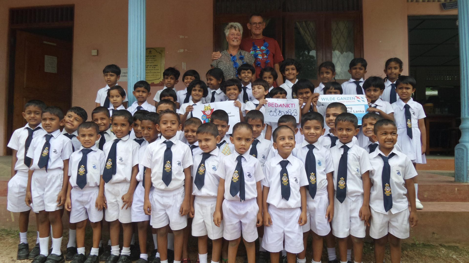 Een klas kinderen in schooluniform poseren voor een foto.