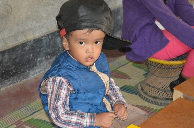 Een jongetje met een beperking kijkt in de camera in India.