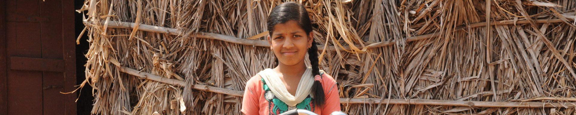 Een meisje poseert met haar fiets in India.